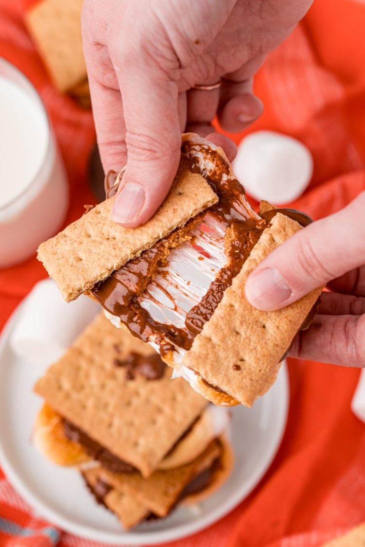 Close up photo of a woman's hand breaking an air fryer smores in half.