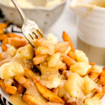 Close up photo of poutine with a fork taking a bite out of it.