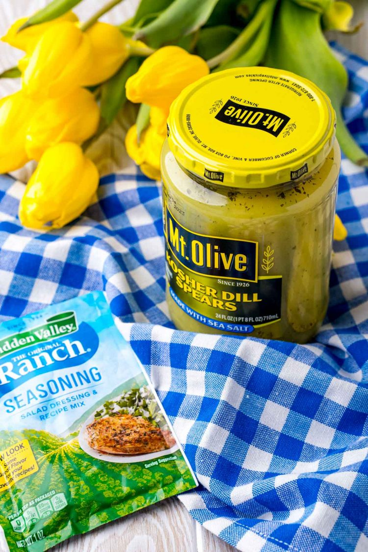 A packet of ranch seasoning and a jar of pickles on a blue gingham napkin.