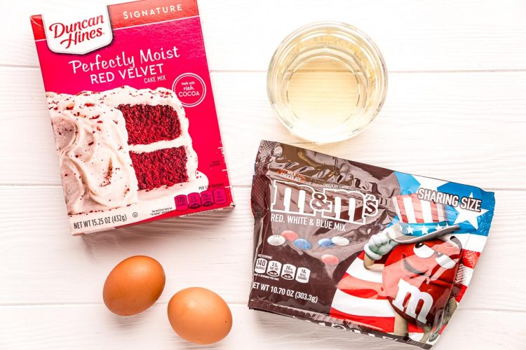 Ingredients used to make 4th of july cookies on a white wood table.