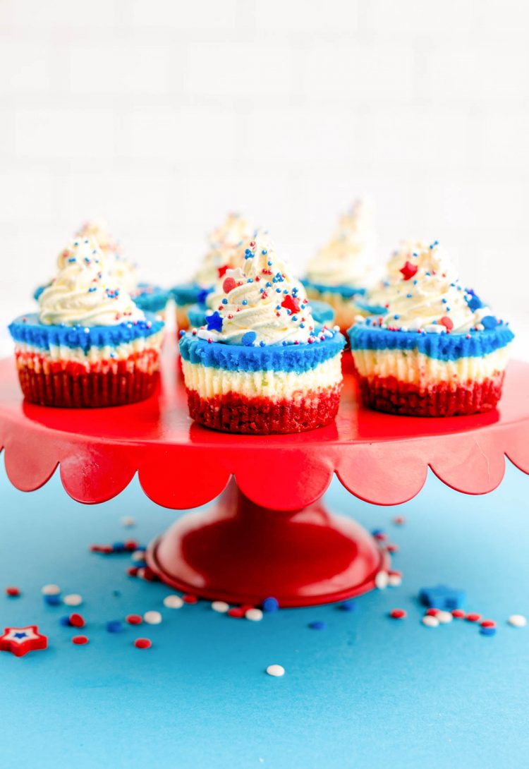 red, white, and blue mini cheesecakes for the 4th of july on a red cake stand on a blue surface.
