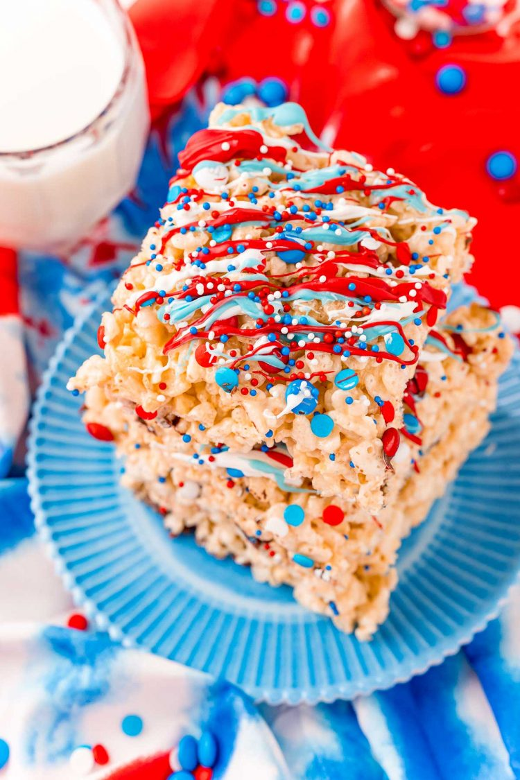 Close up photo of a stack of three rice krispie treats with red, white, and blue candy drizzle and sprinkles.