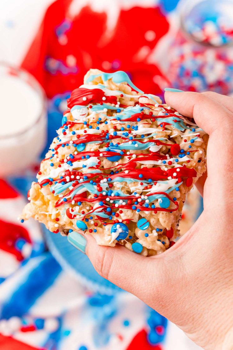 A woman's hand holding a red, white, and blue rice krispie treat to the camera.