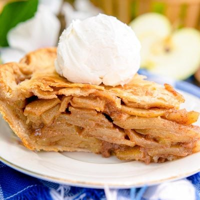 Close up photo of a slice of apple pie on a blue and white checkered napkin.