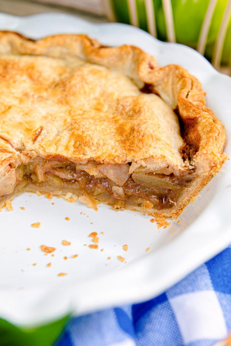 Apple pie in a white pie dish with some pieces missing.