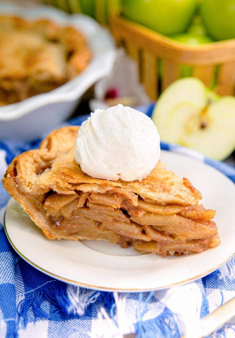 Close up photo of a slice of apple pie on a white plate on a blue gingham napkin with a basket of apples and the rest of the pie in the background.