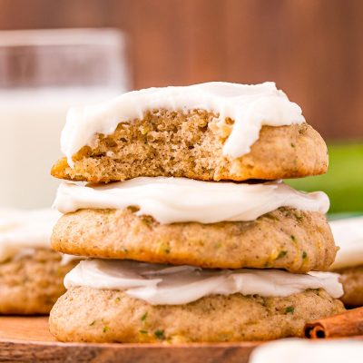 Close up photo of a stack of three zucchini cookies with frosting on a wooden plate on a blue napkin.
