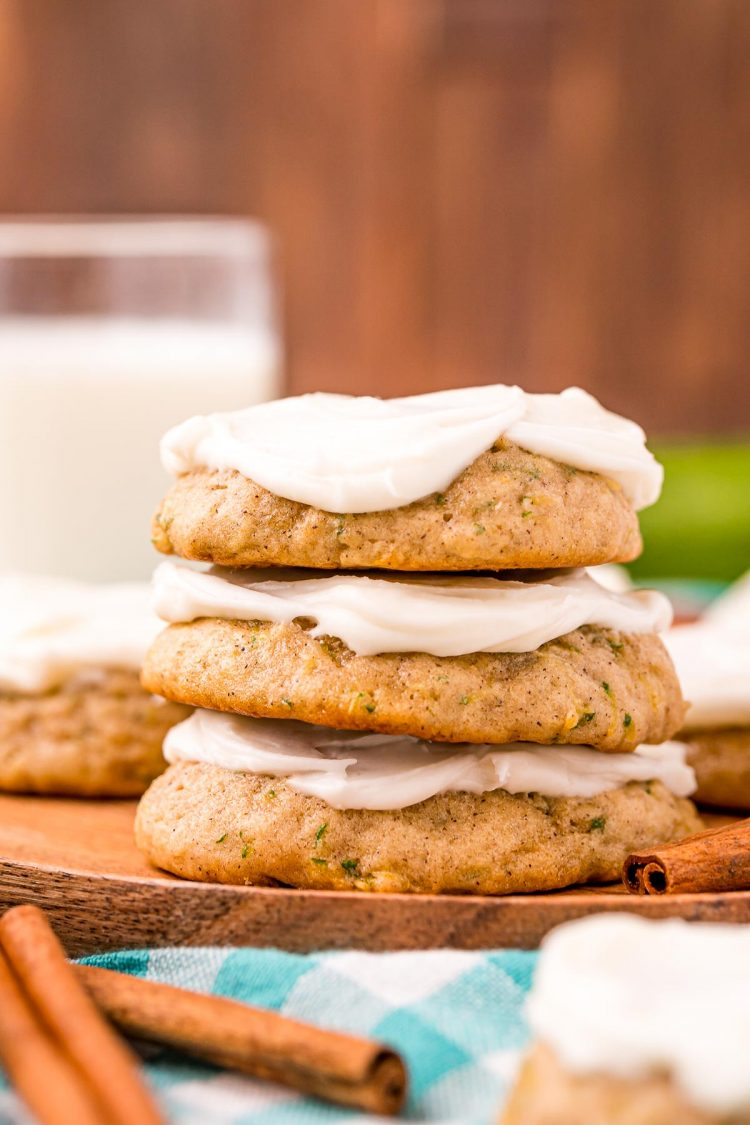 A stack of three frosted zucchini cookies on a wooden plate with more cookies and a glass of milk in the background.