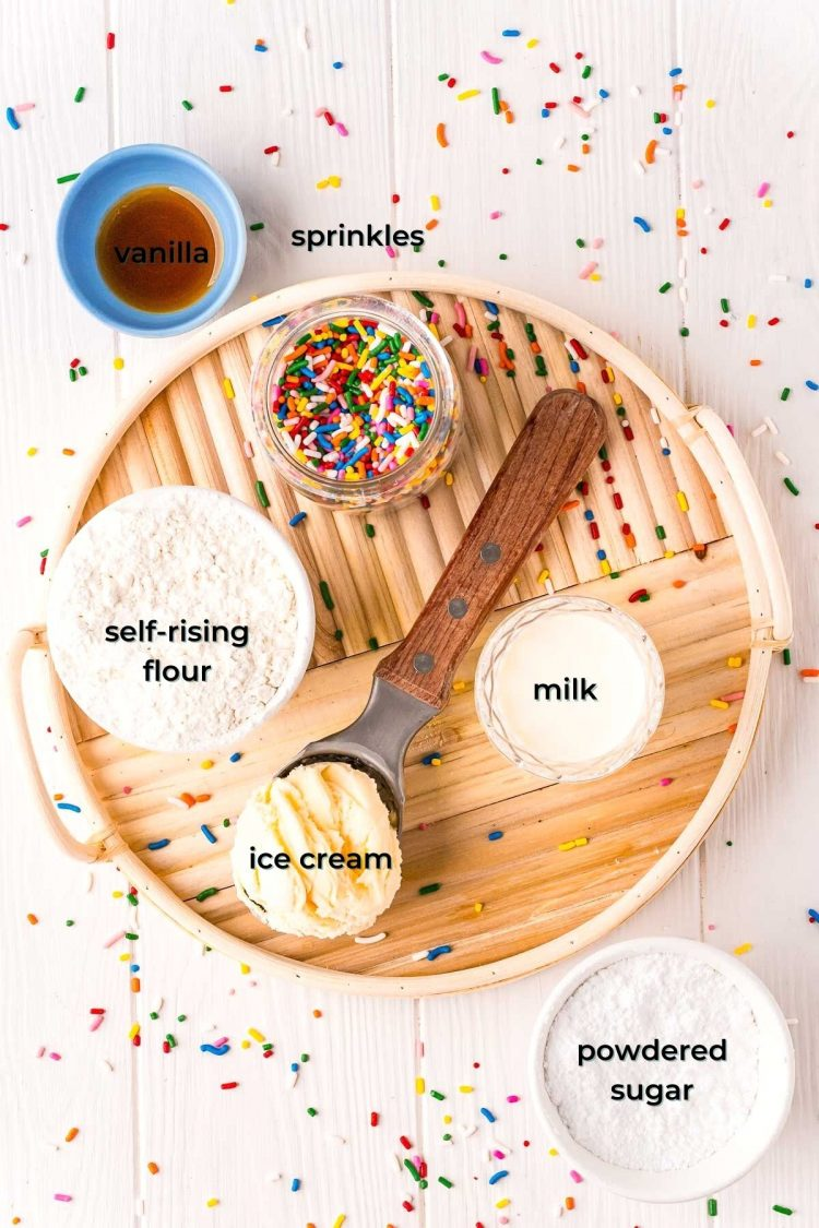 Overhead photo of ingredients used to make funfetti ice cream bread on a white table on a rattan tray with sprinkles scattered all around it.
