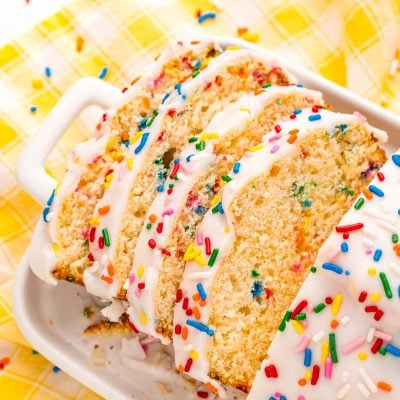 Close up photo of a slice of iced ice cream bread covered in rainbow sprinkles on a white plate on a yellow napkin.