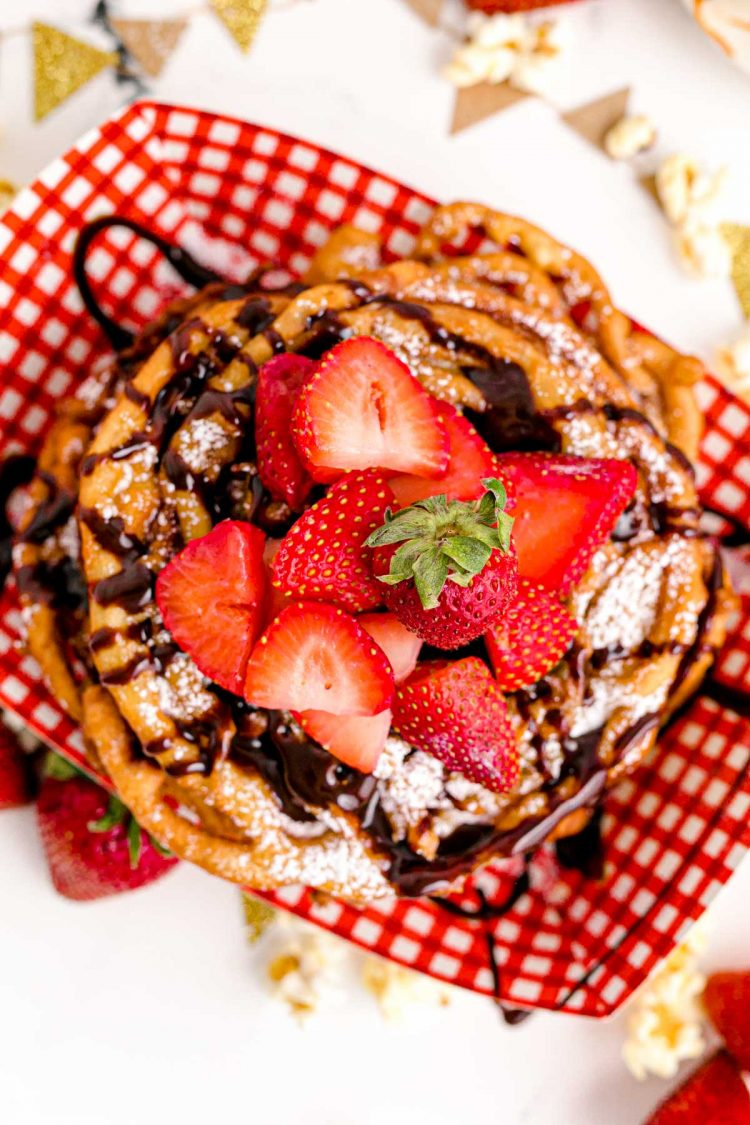 Overhead photo of funnel cakes in a red and white checkered food basket topped with strawberries and chocolate sauce.