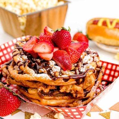 Close up photo of funnel cakes topped with powdered sugar, chocolate sauce, and fresh sliced strawberries in a paper tray.