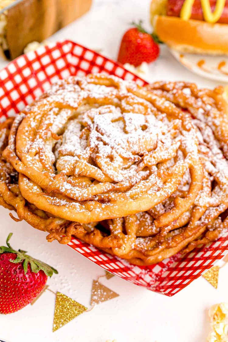 Funnel cakes in a red and white food basket topped with powdered sugar.