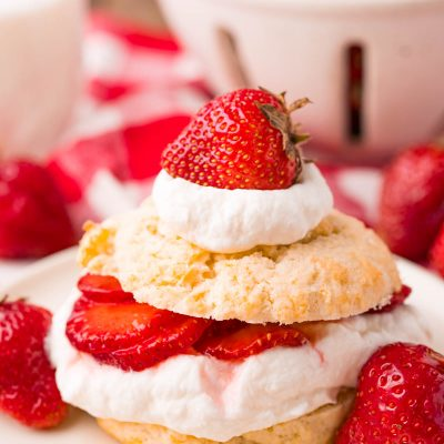 Close up photo of strawberry shortcake on a beige plate on a red and white checkered napkin.