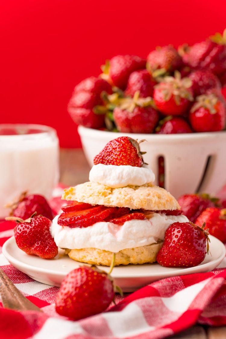 Straight on photo of strawberry shortcake on a white plate on a red and white checkered napkin.