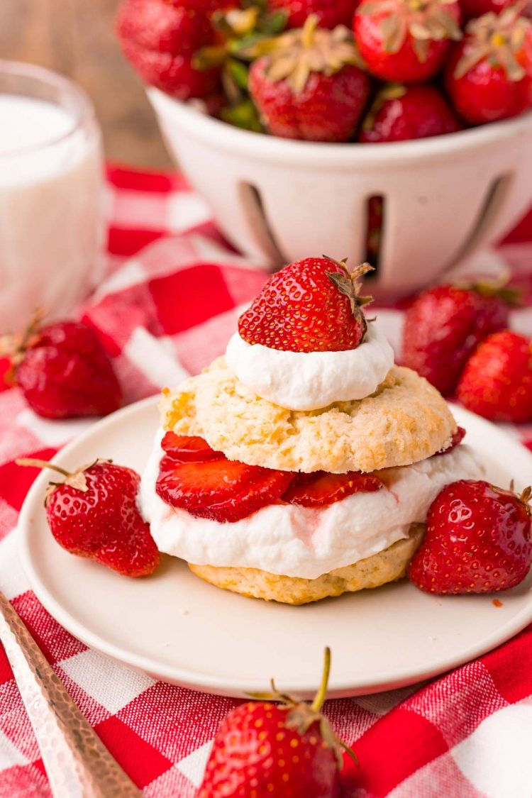 Strawberry shortcake on a tan plate on a red and white checkered napkin.