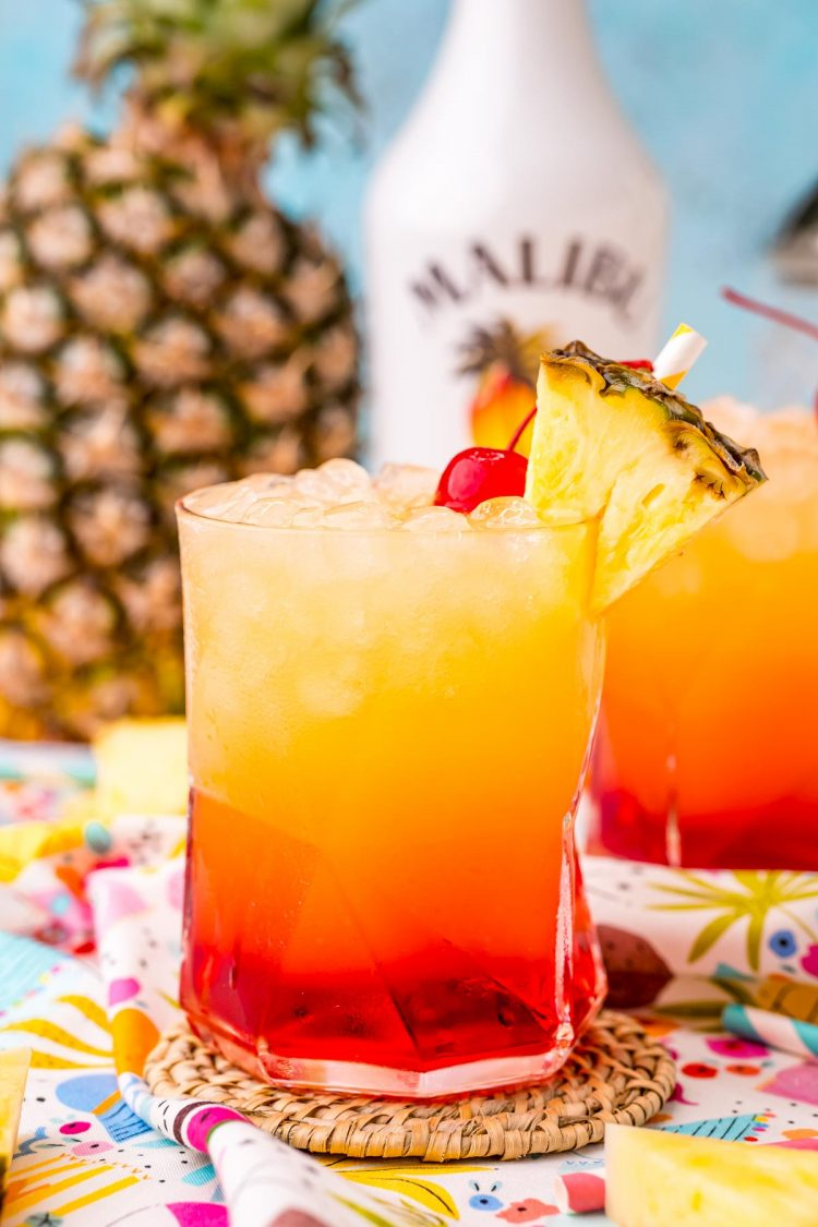Close up photo of a Malibu sunset drink on a colorful napkin with another glass and pineapple in the background.