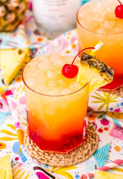 Close up photo of a Malibu Sunset drink on a colorful printed napkin with pineapple wedges and another drink in the background.
