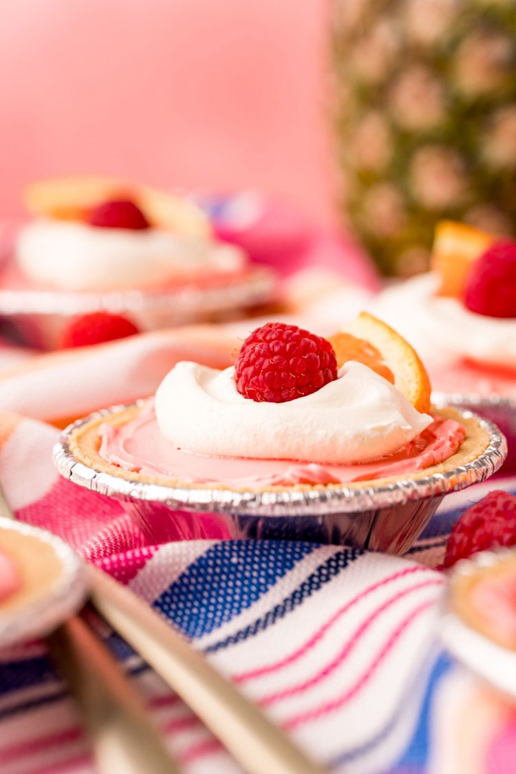 Close up photo of a mini kool-aid pie on a pink, white, and blue striped napkin.
