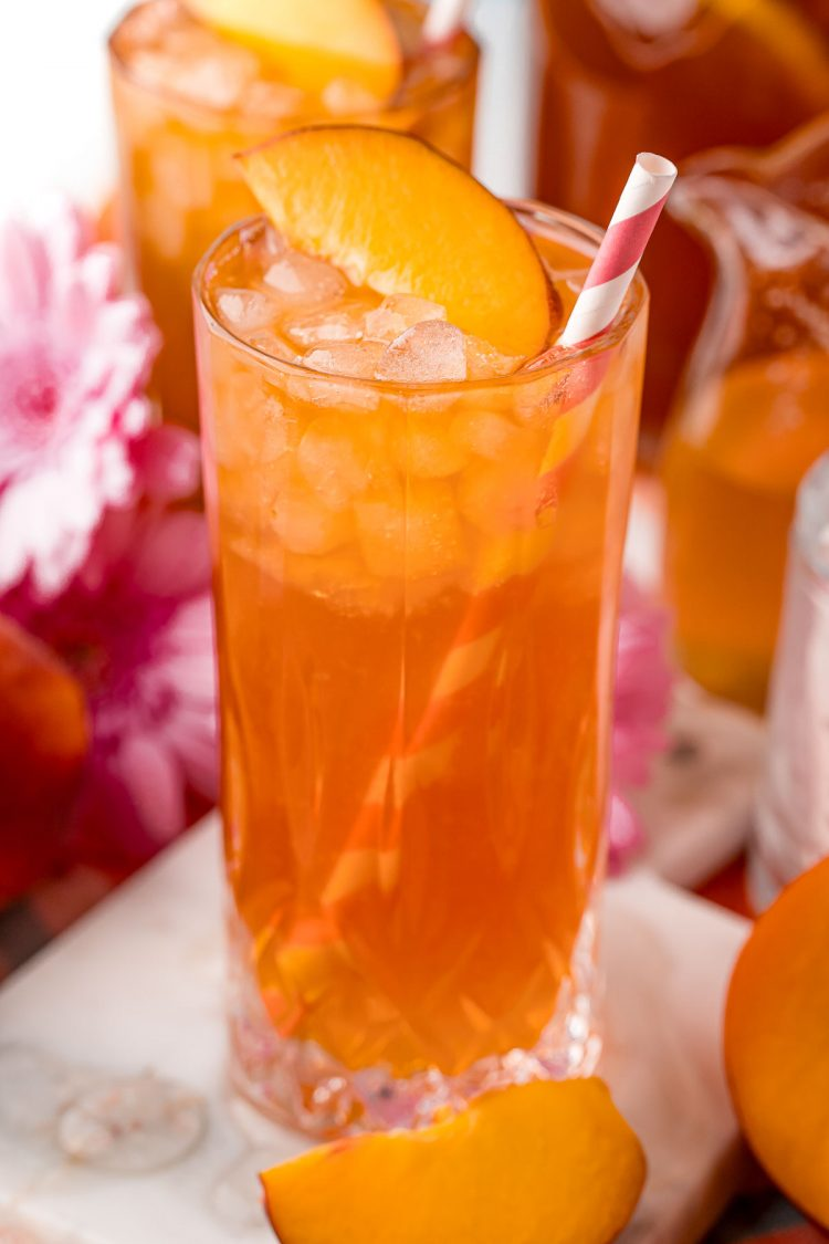 Close up photo of a glass with iced peach tea in it with another glass in the background.