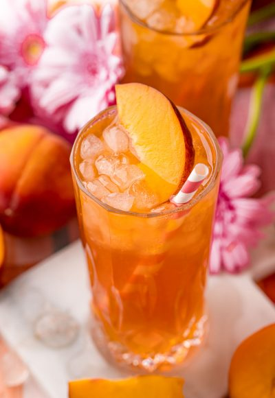 Close up photo of a glass of peach iced tea on a white marble coaster with peaches and pink flowers in the background.