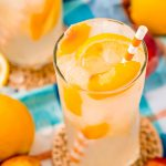 Close up photo of a glass with peach lemonade with lemons and peaches in it and an orange striped straw.