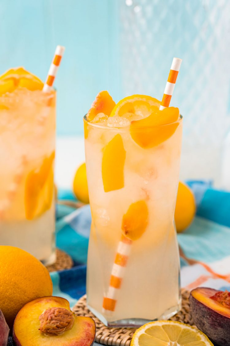 Two glasses of peach lemonade on coasted on a table with peaches scattered around.