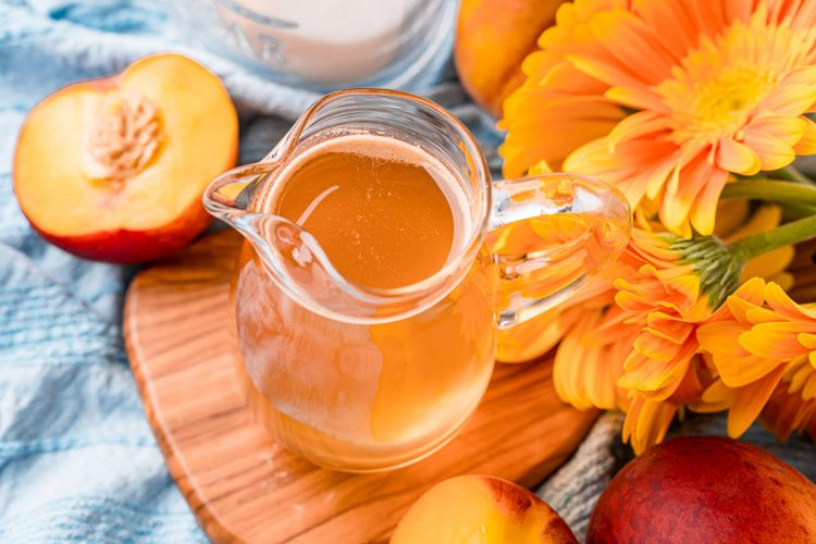 Horizontal photo of a small pitcher of peach simple syrup on a wooden cutting board.
