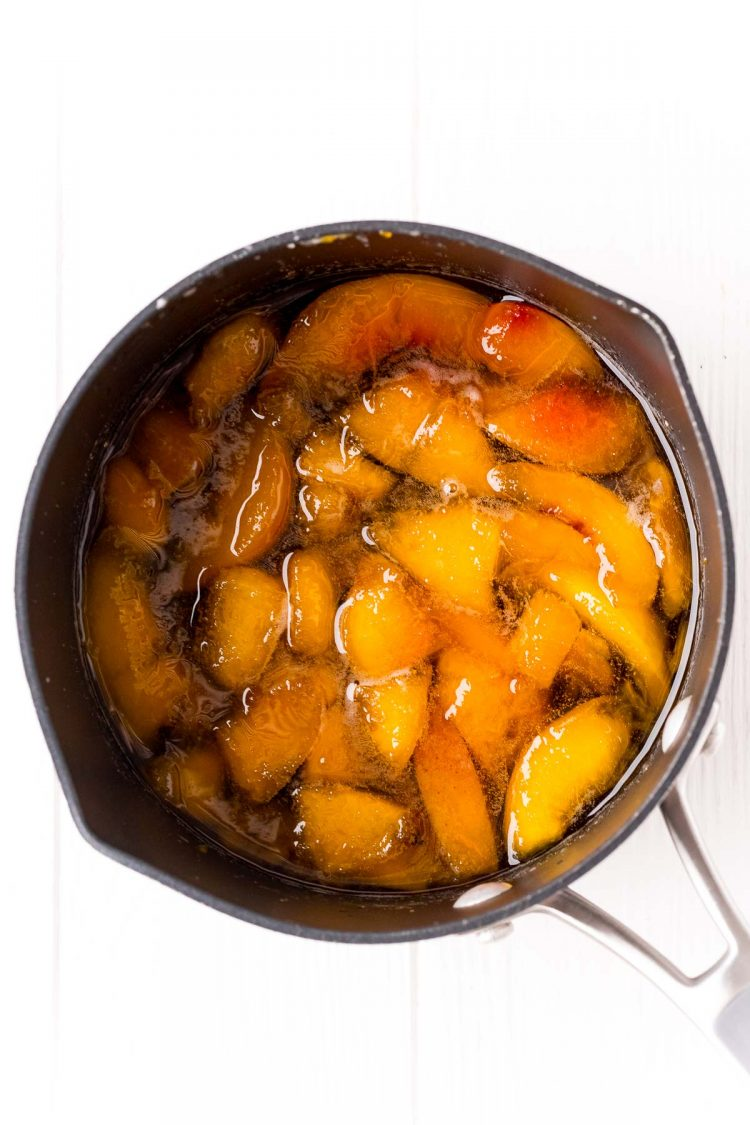 Overhead photo of peach simple syrup being made in a saucepan.