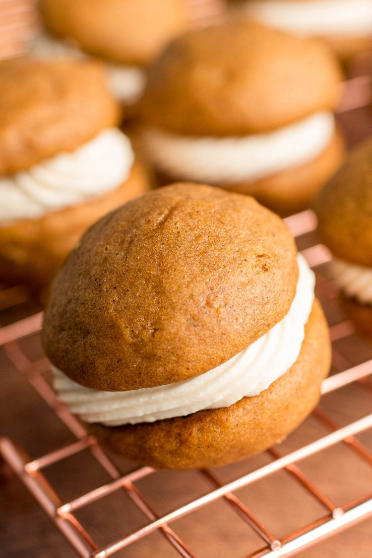 Close up photo of a pumpkin whoopie pie on a copper wire rack with more in the background.