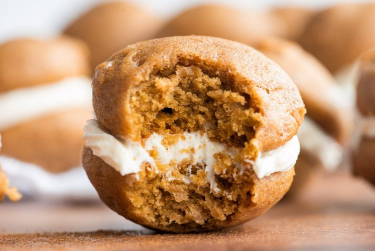 Close up photo of a pumpkin whoopie pie with a bite taken out if it.