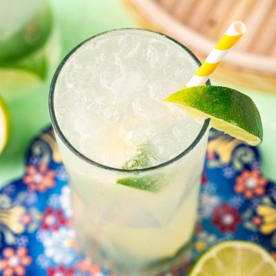 Close up photo of a ranch water cocktail on a colorful trivet with a white and yellow striped paper straw and lime wedges.