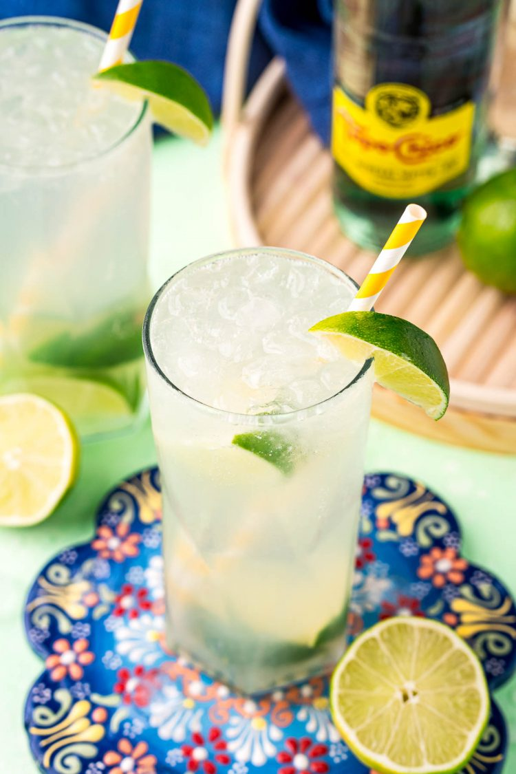 Highball glasses with ranch water in them on a colorful trivet surrounded by limes.