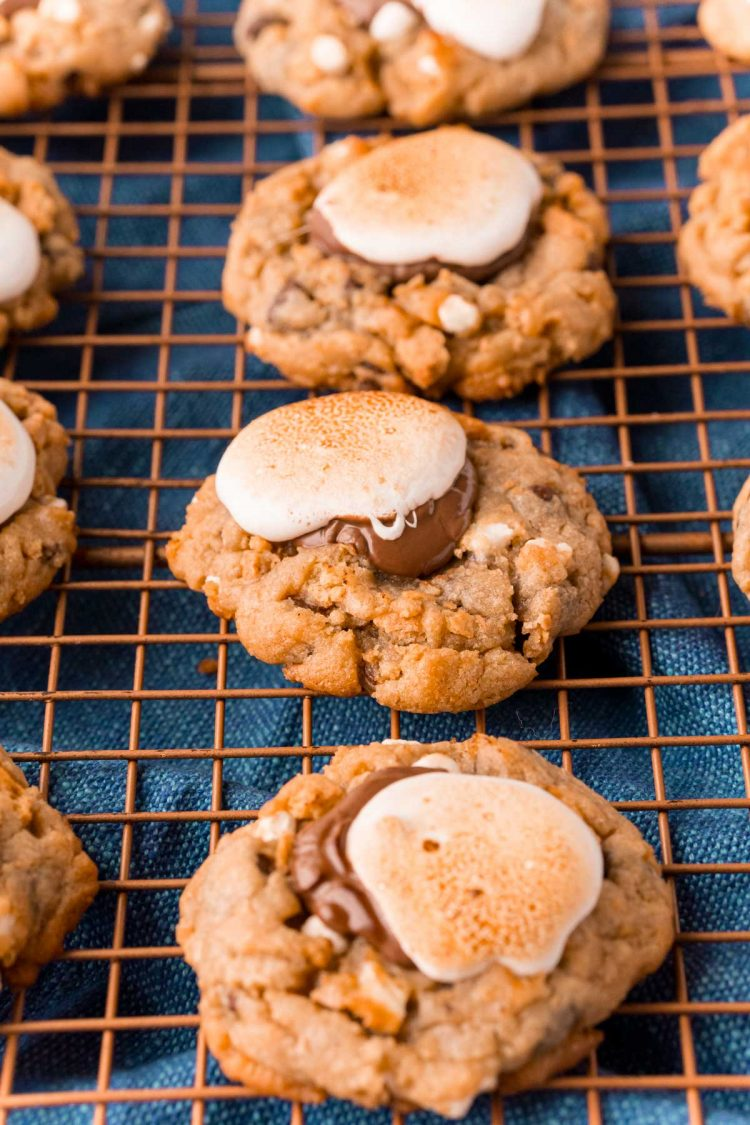 Close up photo of rows of s'mores cookies on a wire rack on a blue napkin.