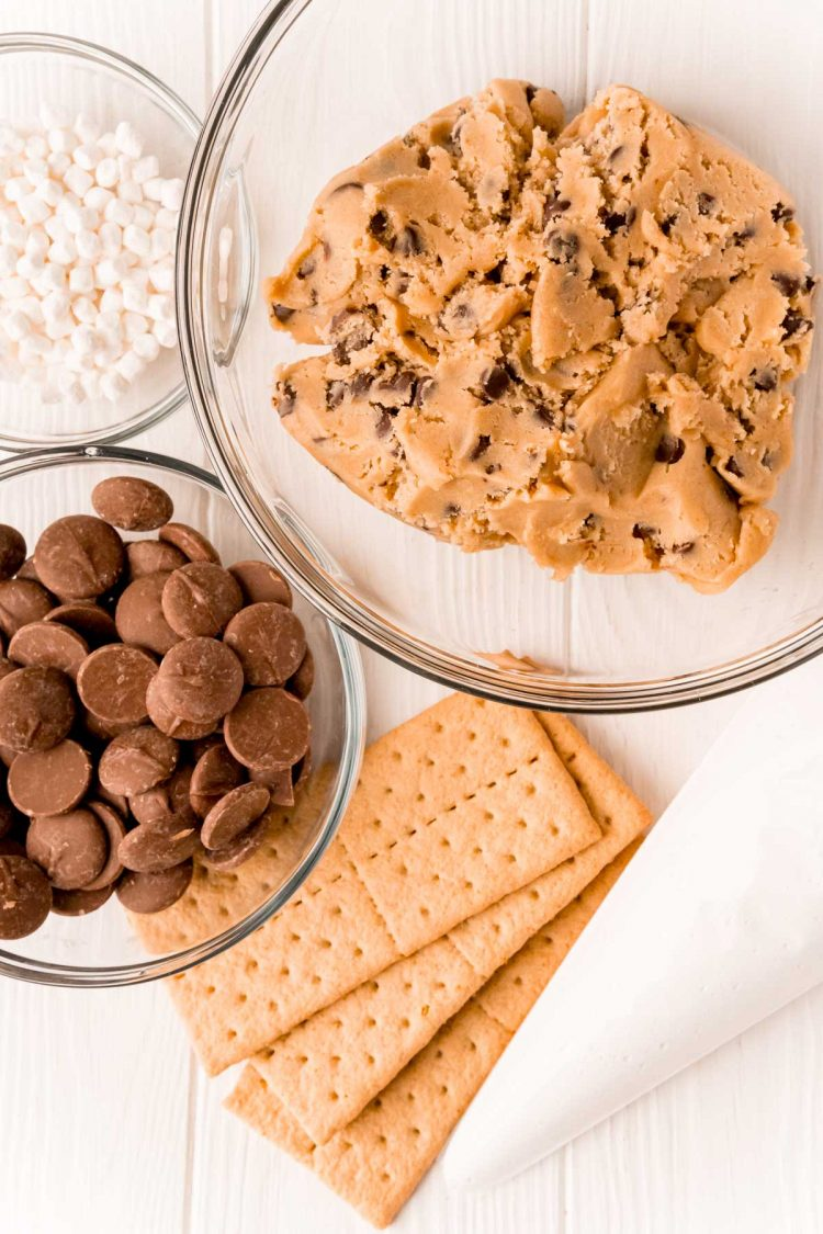 Overhead photo of ingredients to make smores cookies on a white table.