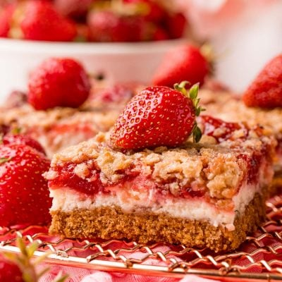 Close up photo of strawberry cheesecake bars on a copper wire rack on a pink napkin.