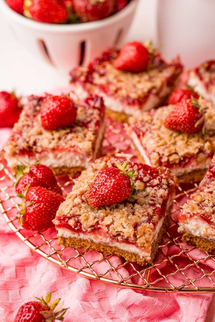 Close up photo of strawberry cheesecake bars on a wire rack on a pink napkin.