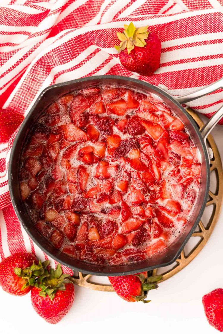 Overhead photo of a saucepan with strawberries in it to make strawberry simple syrup.