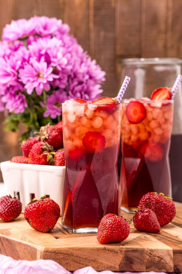 Photo of two glasses on strawberry sweet tea on a wooden board with strawberries scattered around and purple flowers in the background.
