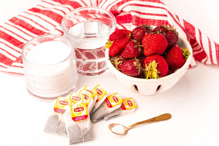 ingredients used to make strawberry sweet tea on a white table with a white and red striped napkin.