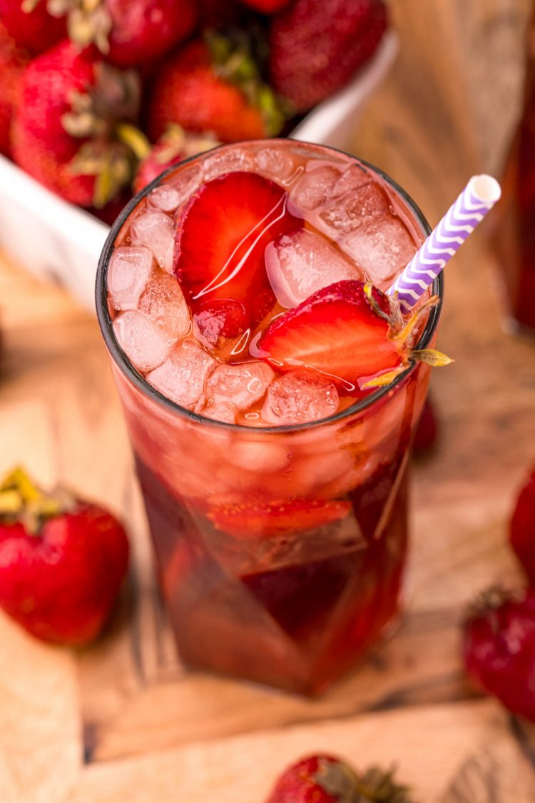 Close up photo of a glass of strawberry sweet tea on a wooden board with strawberries scattered around.