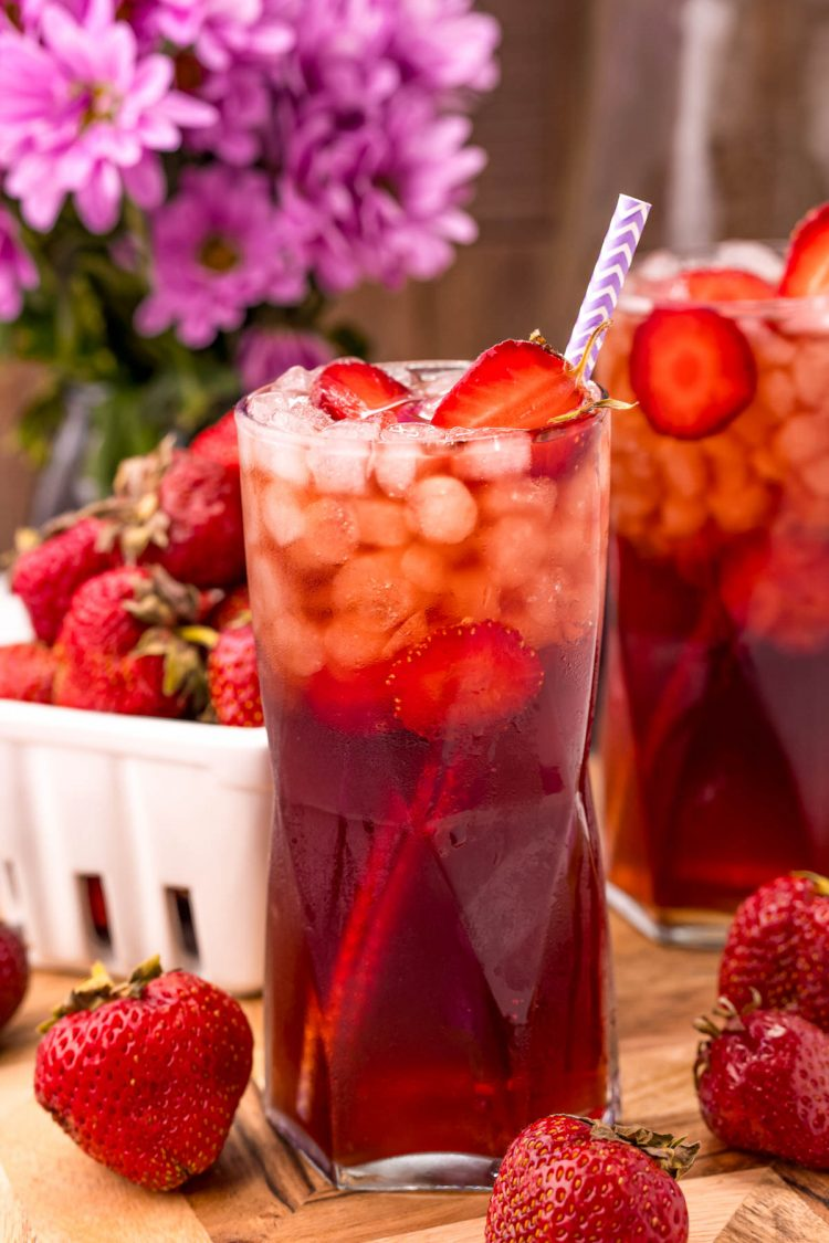 Close up photo of a glass of strawberry tea with another glass and a carton of strawberries in the background.