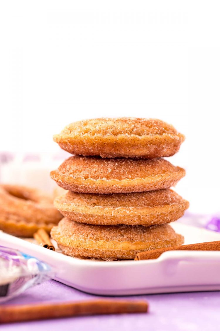 4 uncrustables donuts stacked on top of each other on a white serving tray on a purple surface.
