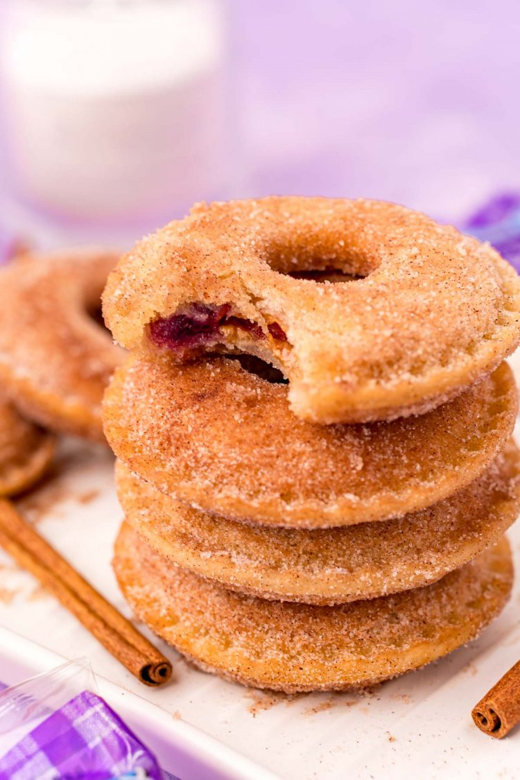 Close up photo of a stack of Uncrustables donuts on a white tray with the top one missing a bite.