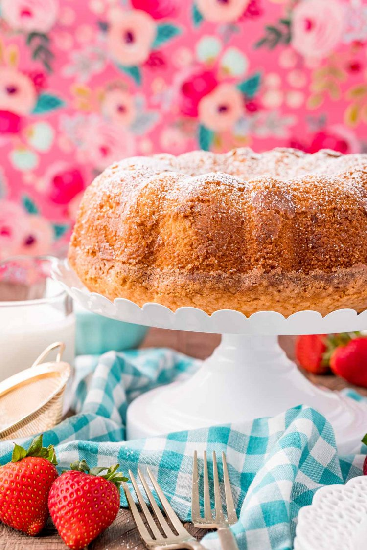 Whipping cream cake on a white cake stand on a blue gingham napkin with a pink floral background.