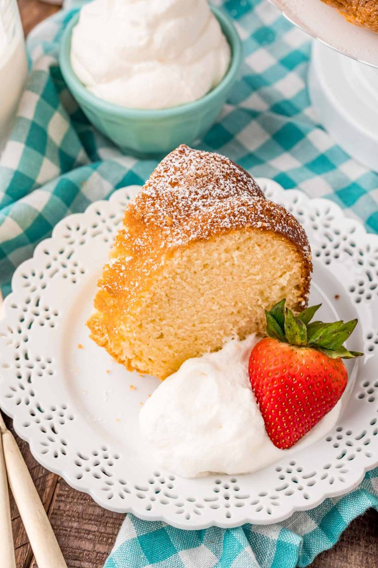 A slice of whipping cream cake on a white plate with whipped cream and a strawberry on a teal gingham napkin.