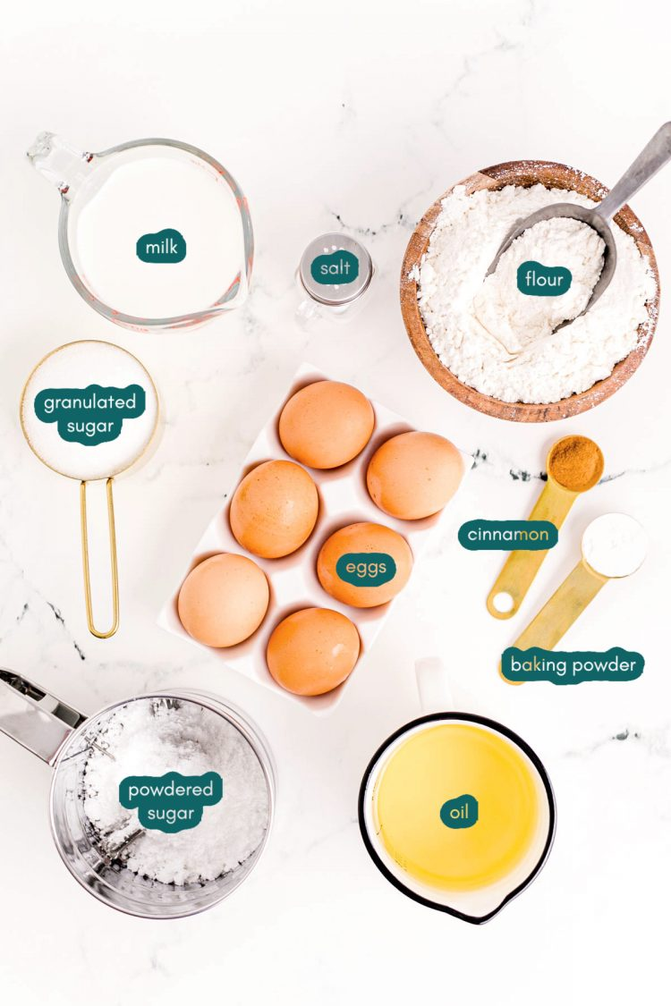 Overhead photo of ingredients to make funnel cakes prepped on a white counter.