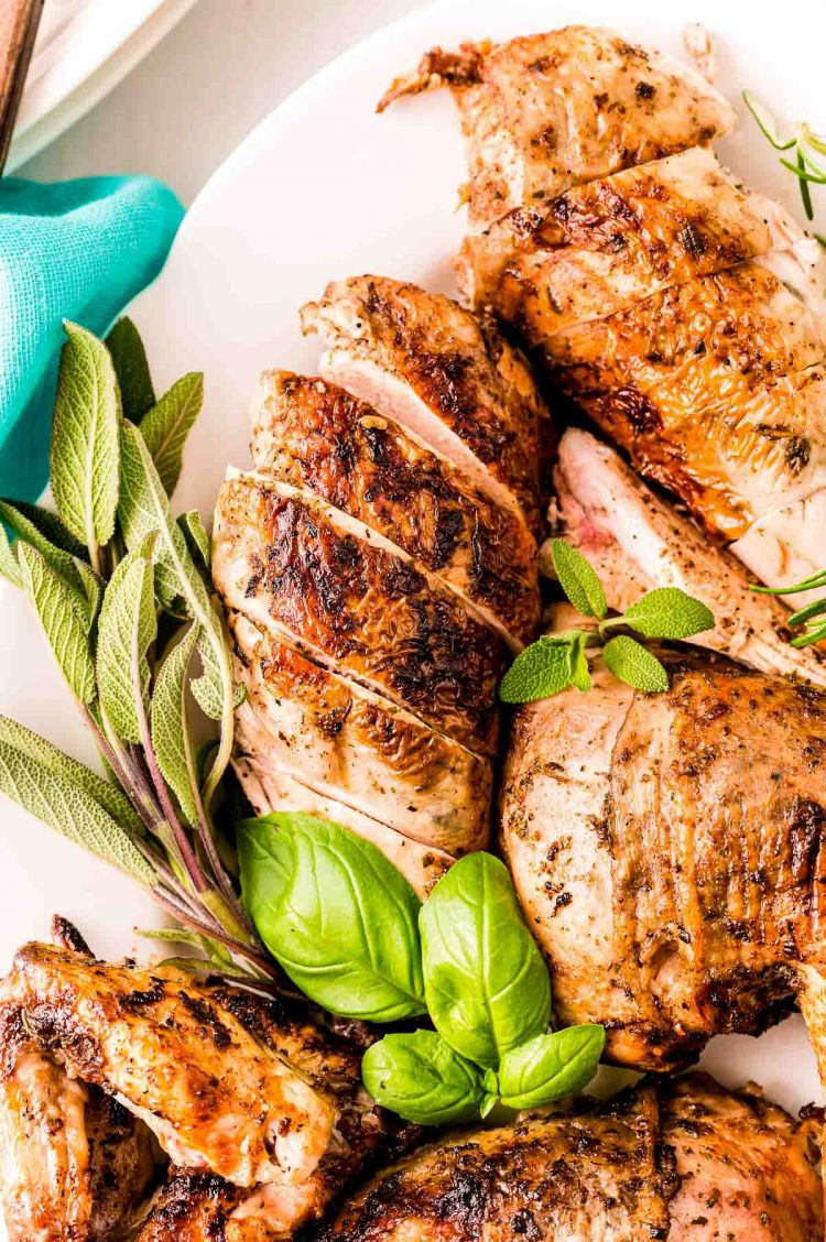 Grilled Italian chicken on a white plate with herbs.