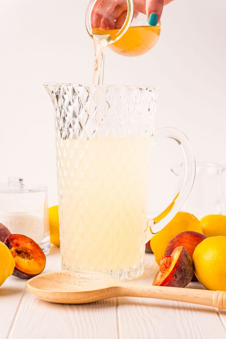 Photo of peach simple syrup being poured into a large pitcher to make lemonade.