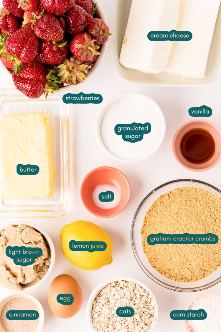 Ingredients to make strawberry cheesecake bars prepped on a white table.